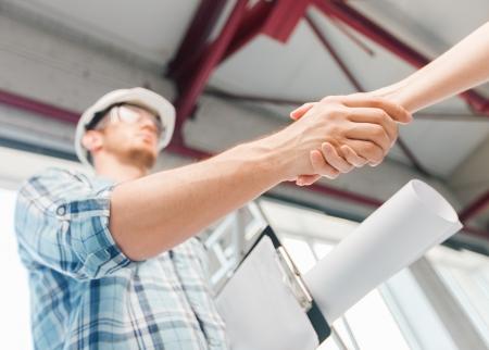 alba�il: la arquitectura y el concepto de rehabilitaci�n de viviendas - constructor con el modelo que sacude la mano pareja