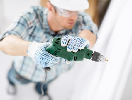 taladro: diseño de interiores y el concepto de rehabilitación de viviendas - hombre en el casco con el taladro eléctrico hacer el agujero en la pared