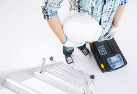 architect and home renovation concept - man with ladder, helmet and toolkit photo