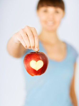 healthy food and lifestyle - woman hand holding red apple with heart shape photo