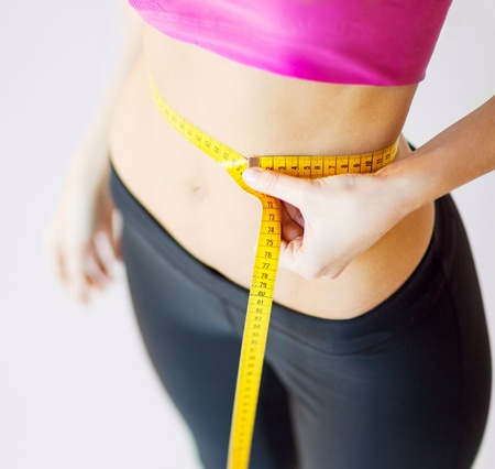 sport and diet concept - trained belly with measuring tape photo