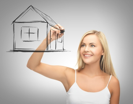 real estate, technology and accomodation concept - woman drawing house on virtual screen photo