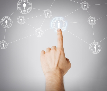 business, technology, internet and networking concept - man hand pressing button with contact on virtual screens Stock Photo