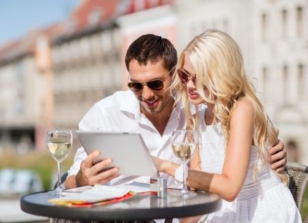 cafe internet: vacaciones de verano, las citas y la tecnología concepto - pareja en busca de tablet pc en la cafetería en la ciudad