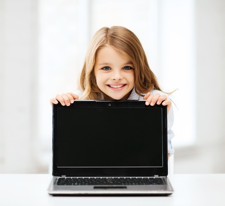home school: education, school, technology and internet concept - little student girl showing laptop pc at school Stock Photo