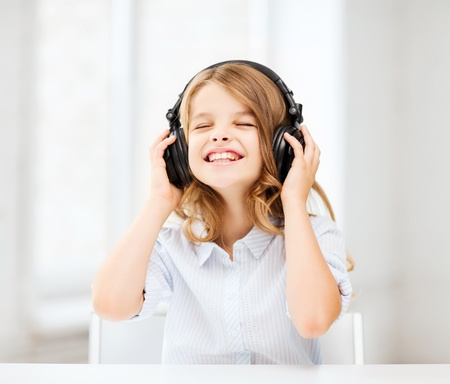 child singing: home, technology and music concept - little girl with headphones listening to music and singing