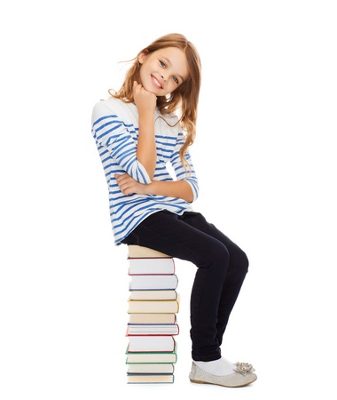 girl sit: education and school concept - little student girl sitting on stack of books
