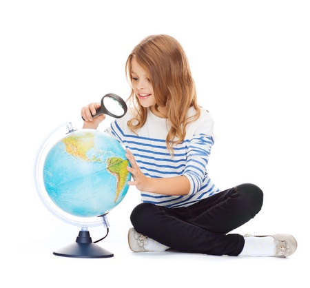 education and school concept - little student girl looking at globe with magnifier