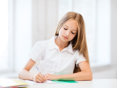 education and school concept - little student girl studying at school photo