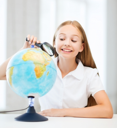 education and school concept - little student girl looking at globe with magnifier at school photo
