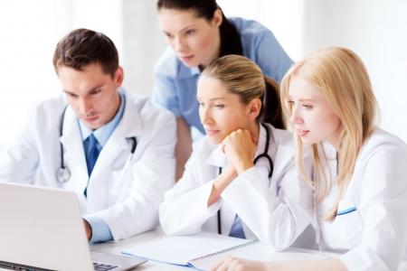 건강, 의료 및 기술 개념 - 노트북을 찾고 의사의 그룹