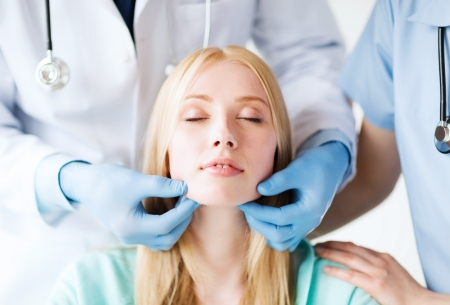 facial: healthcare, medical and plastic surgery concept - plastic surgeon or doctor with patient Stock Photo