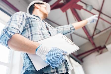 renovation de maison: l'architecture et le concept de la r�novation domiciliaire - homme dans le casque et les gants avec le mod�le dans l'usine