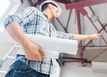 architectuur en renovatie van woningen concept - man in helm en handschoenen met blauwdruk die de richting
