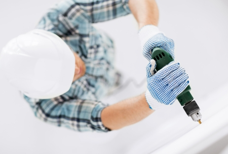 interior design and home renovation concept - man in helmet with electric drill making hole in wall Stock fotó