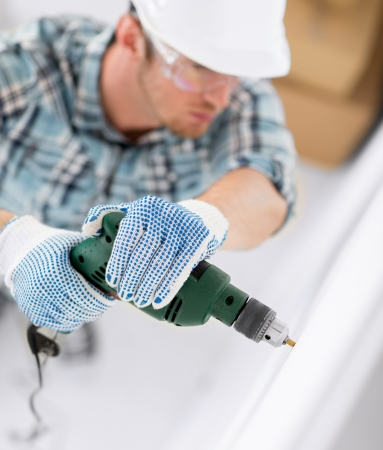 interior design and home renovation concept - man in helmet with electric drill making hole in wall photo