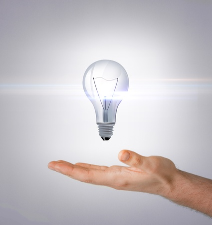 energy and environment concept - man hand with light bulb photo