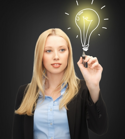 brilliant idea: business, energy and environment concept - woman drawing light bulb on the virtual screen Stock Photo