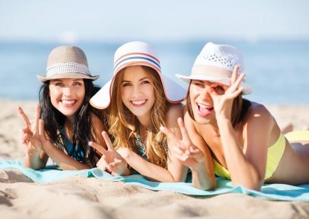 zomervakantie en vakantie - meisjes in bikini te zonnen op het strand Stockfoto