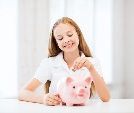 education, school and money saving concept - child putting coins into piggy bank Stock Photo