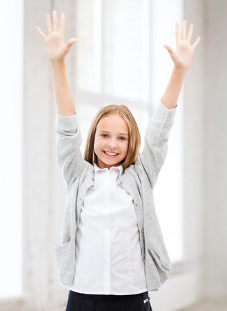 education and school concept - little student girl with hands up at school photo
