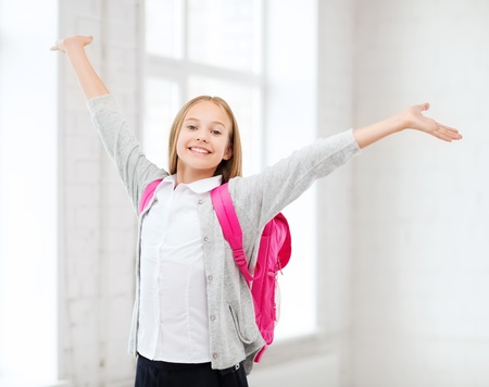 answering: education and school concept - little student girl with hands up at school