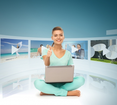 technology, internet, tv and news concept - young woman with laptop pc and virtual screens photo