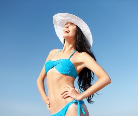 summer holidays and vacation concept - girl in bikini standing on the beach photo