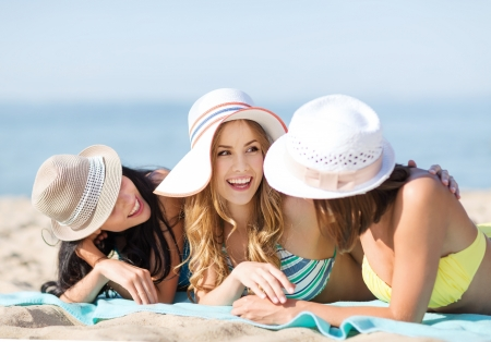 chilling out: summer holidays and vacation - girls in bikinis sunbathing on the beach