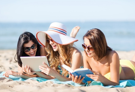 summer holidays, technology and internet concept - girls in bikinis with tablet pc sunbathing on the beach photo
