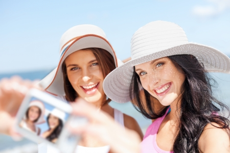 headwear: summer holidays and vacation concept - girls taking self portrait on the beach