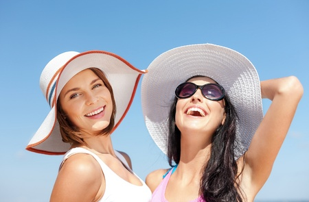 summer holidays and vacation concept - girls in hats on the beach photo