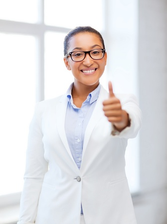 business and education concept - african businesswoman showing thumbs up in office photo