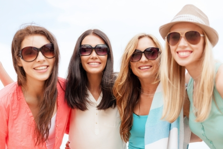 women friends: summer holidays, vacation and beach activities - girls in shades having fun on the beach