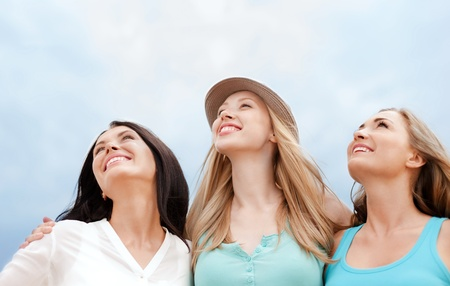 people looking up: summer holidays and vacation concept - girls looking up in the sky Stock Photo
