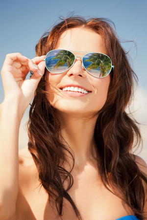 holidays and beach concept - beautiful woman in bikini and sunglasses Фото со стока
