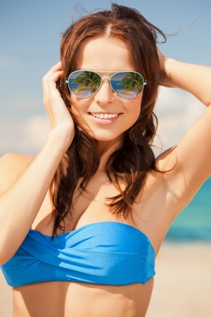 holidays and beach concept - beautiful woman in bikini and sunglasses Stock Photo - 22183520