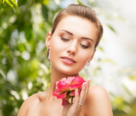 beauty, holidays and jewelry - woman with diamond earrings, ring and flower photo