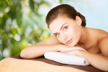bliss: beauty, holidays and spa concept - woman in spa salon lying on the massage desk