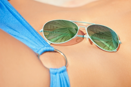 holidays, beach and shades advertisement concept - sunglasses laying on woman body photo
