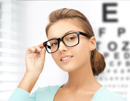 medicine and vision concept - woman in eyeglasses with eye chart Stock Photo