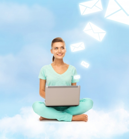 education and technology concept - young woman sitting on the cloud with laptop photo