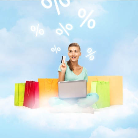 internet shopping and future technology concept - woman with laptop, shopping bags and credit card on the cloud photo