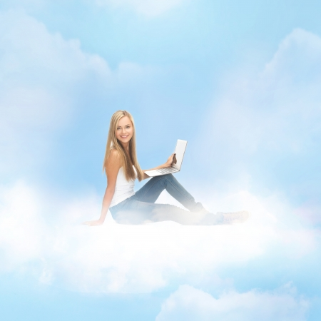 education and technology concept - young woman sitting on the cloud with laptop Stock Photo - 22183850