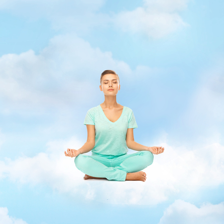 relaxation, meditation and lifestyle concept - girl on the cloud in lotus position and meditating photo