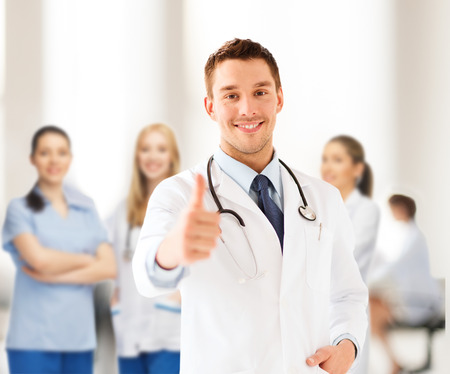 healthcare and medical concept - doctor with stethoscope showing thumbs up photo