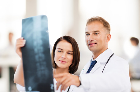 radiology: healthcare, medical and radiology concept - two doctors looking at x-ray