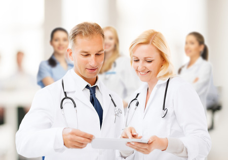 healthcare and technology concept - two doctors looking at tablet pc photo