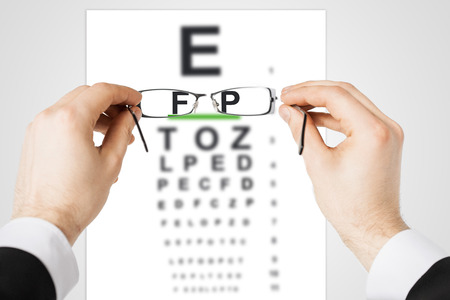 eyesight: medicine and vision concept - man looking at eye chart through eyeglasses