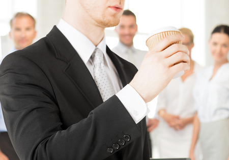 take time out: business concept - man holding take away coffee cup